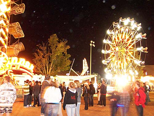 2007 Acton Ontario Fall Fair. A ride spins in the night while the crowd gathers