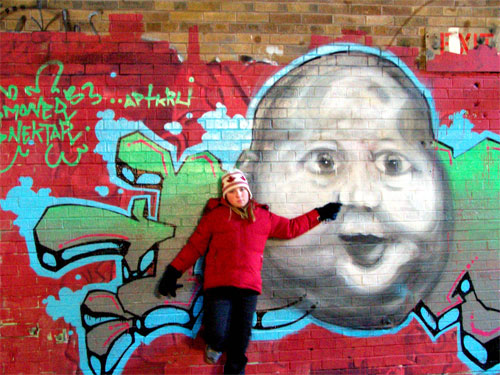 Toronto Don Valley Brickworks. Inside brick factory. Erin stands beside baby graffiti face.